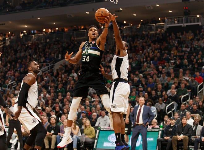 Bucks forward Giannis Antetokounmpo finds space to shoot around Clippers forward Kawhi Leonard.