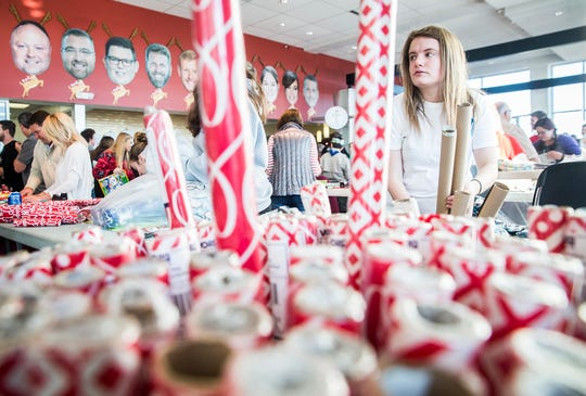 Rolls of wrapping paper are prepped for volunteers at Toyota of Muncie during Secret Families of Delaware County Saturday morning. Each sponsored family received a Christmas tree, Bible, a $50 gift card, and presents delivered to their homes by volunteers.