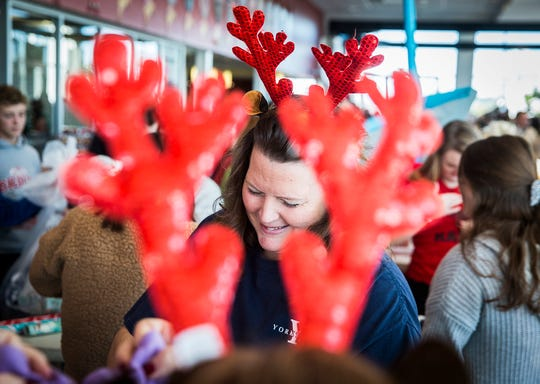 Volunteers work in shifts throughout the morning at Toyota of Muncie during Secret Families of Delaware County Saturday. Each sponsored family received a Christmas tree, Bible, a $50 gift card, and presents delivered to their homes by volunteers.