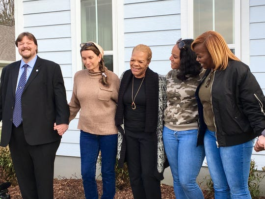 Brenda Wilson, center, smiles while Rev. Becca Stevens, second from left, founder of Thistle Farms program for women survivors of addiction and trafficking, offers a prayer at the dedication of Wilson's Habitat for Humanity-built home Dec. 6, 2019