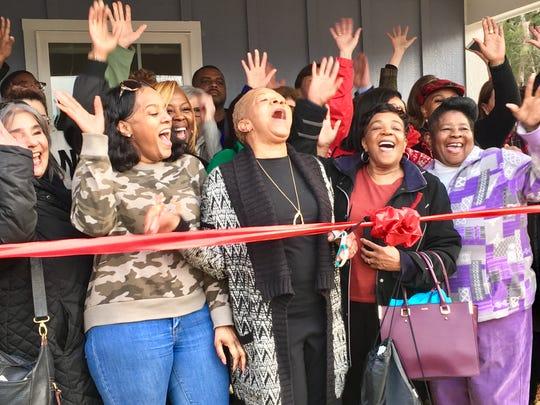 Brenda Wilson, front and center, cuts the ribbon on her new Habitat for Humanity home in Nashville with about 30 of her friends, relatives and coworkers. Wilson was one of dozens of home former President Jimmy Carter, Garth Brooks, Trisha Yearwood and hundreds of volunteers helped build in October as part of Jimmy and Rosalynn Carter Work Project 2019 in Nashville.
