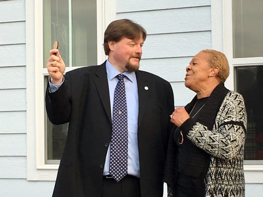 Jeremy Heidt of the Tennessee Housing Development Agency hands Brenda Wilson the keys to her new home in a Habitat for Humanity development in northern Nashville Dec. 6, 2019