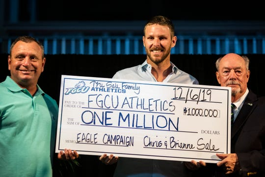 From left to right, FGCU's baseball head coach Dave Tollett, Chris Sale of the Boston Red Sox, and FGCU President Michael V. Martin hold a $1 million check during Night at the Nest Gala on Friday, December 6, 2019, at Alice Arena in Florida Gulf Coast University.