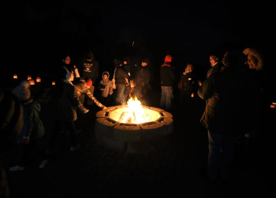 A crowd gathers round a bonfire, Friday, Dec. 6, 2019, during Riverglo in Farmington.