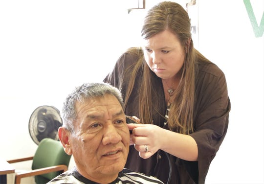 From right, AmeriCorps member Jennifer Arthur cuts San Juan Chapter President and Army veteran Sam Bee's hair on Dec. 6 at the San Juan Chapter house in Lower Fruitland.