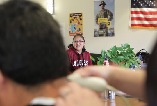 Terri Deale, AmeriCorps member at Tsé Daa K'aan Chapter, watches a veteran receive a haircut on Dec. 6 at the San Juan Chapter house in Lower Fruitland.