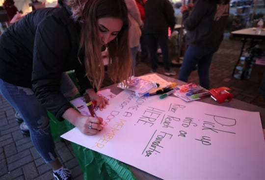 Farmington High School junior Angeleesa Aragon makes a sign, Friday, Dec. 6, 2019, while volunteering with the National Honor Society during Riverglo in Farmington.