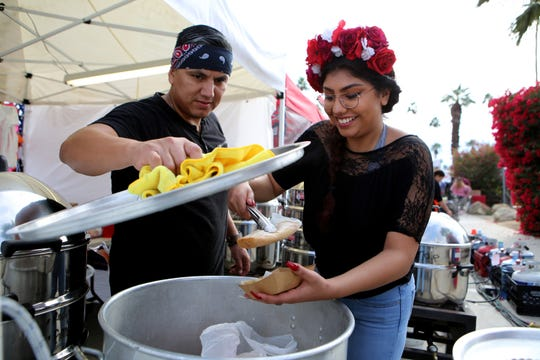 Robert Gandara, left, and Brianna Galvan of Tijuana Bakery Cafe get tamales for customers during the Indio International Tamale Festival in Indio, Calif., on December 7, 2019.