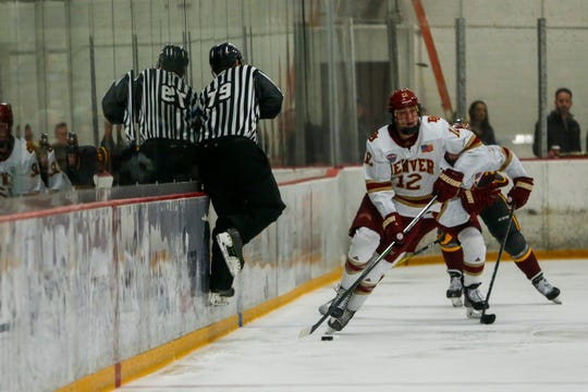 A referee hops over the puck in the second period of the Arizona State Sun Devils game against the Denver Pioneers Friday, December 6, 2019 at Oceanside Ice Arena in Tempe.