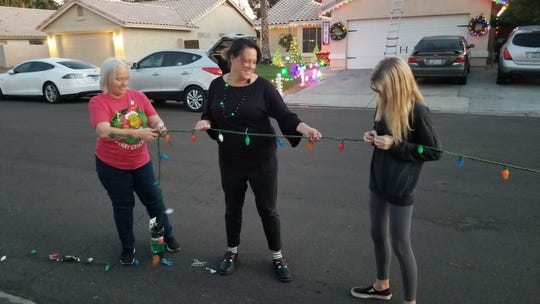 Sherry Karas, left, Beth Kingsley and Taylor Burke tie a strand of lights to paracord.
