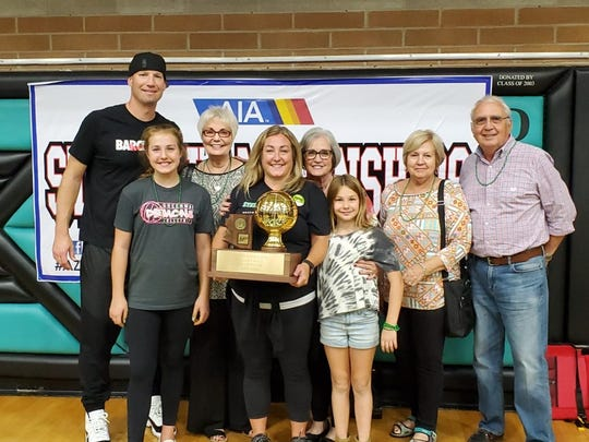 Greenway coach Sarah Peterson stands with her husband and Chaparral boys basketball coach Daniel Peterson and their family as she holds up the 2019 4A girls volleyball championship trophy at Highland HIgh School