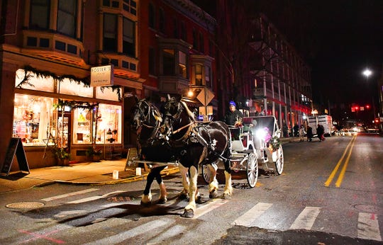 Scott Enslin, of Benchfield Farms which is based in Newville, provides horse-drawn carriage rides during First Friday in York City, Friday, Dec. 6, 2019. Dawn J. Sagert photo