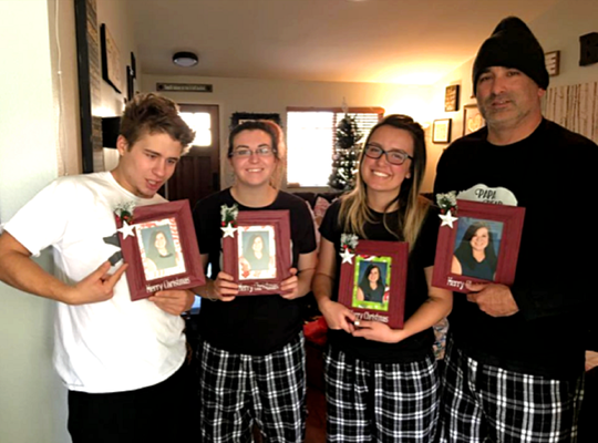 Jennifer Matherly Button's family poses for a photo while holding framed pictures of her that she gifted them for Christmas in 2017.
