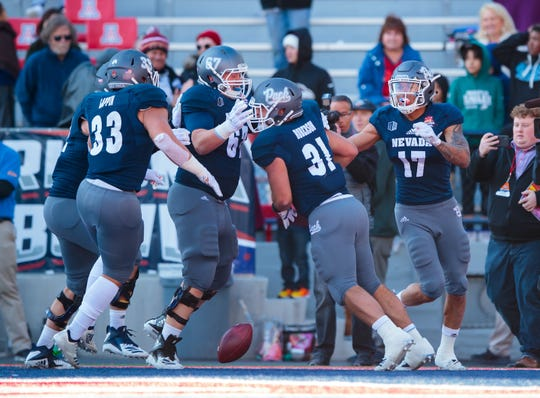 Nevada players celebrate with Wolf Pack tight end Reagan Roberson (31), who scored the winning touchdown in last season's Arizona Bowl against Arkansas State.