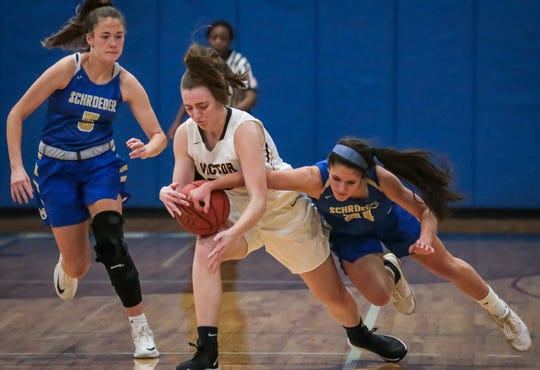 Victor's Kaitlin Murphy battles for possession against Webster Schroeder on Friday. [Dianna Hart/For The Daily Messenger]