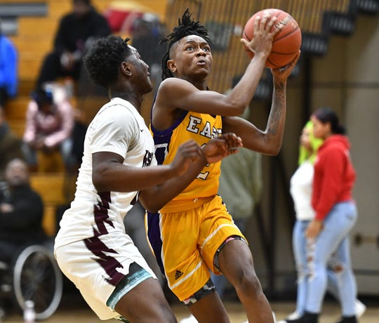 East's Kaori Barley, right, drives to the basket past Edison Tech's Mike Morgan during a regular season game at Edison Career & Technology High School, Friday, Dec. 6, 2019.