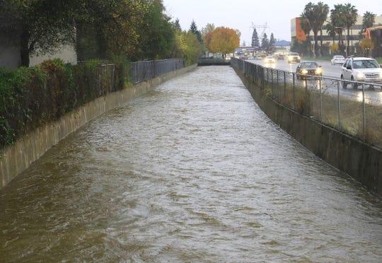 Churn Creek runs high and fast in its concrete channel alongside Churn Creek Road at Presidio Street during heavy rain in Redding on Saturday, Dec. 7, 2019.