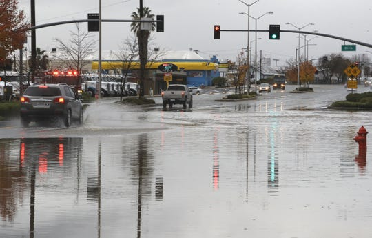 Cars drive through standing water on South Market Street near Ellis Street in Redding after heavy rain fell Saturday, Dec. 7, 2019.