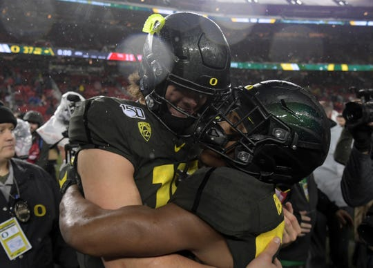 Dec 6, 2019; Santa Clara, CA, USA; Oregon Ducks quarterback Justin Herbert (10) and wide receiver Jaylon Redd (30) embrace  after the Pac-12 Conference championship game against the Utah Utes at Levi's Stadium. Oregon defeated Utah 37-15. Mandatory Credit: Kirby Lee-USA TODAY Sports