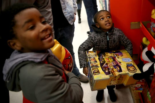 Liam, 3, right, and his brother Justice Stepney, 6, of Salem, pick out toys during a Shop with a Cop event at Walmart in South Salem on Dec. 7, 2019. About 600 kids picked out gifts with law enforcement professionals by their side on Saturday.