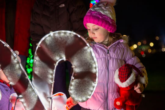 Amelia Ferrera, 4, of Salem, inspects candy cane lights during the 24th Annual Riverfront Park Holiday Tree Lighting Ceremony on Dec. 6 in Salem.