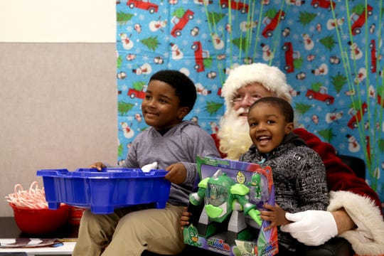 Brothers Justice, 6, left, and Liam Stepney, 3, of Salem, get a photo with Santa during a Shop with a Cop event at Walmart in South Salem on Dec. 7, 2019. About 600 kids picked out gifts with law enforcement professionals by their side on Saturday.