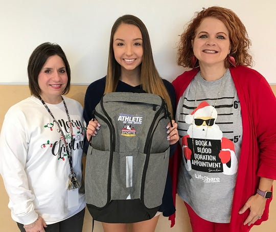 Benton cheerleader McKenzie Murphy (center) poses with Benton cheer sponsor Aimee Aiken (left) and principal Teri Howe with her Times/SBSC Athlete of the Week backpack.