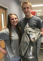 Airline swim coach Brittany Gregg poses with Times/SBSC Athlete of the Week Mack Smith and his AOW backpack.
