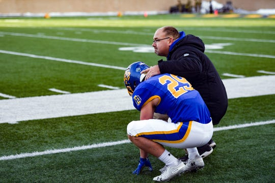 Lance Eide of SDSU is comforted after losing the playoff game on Saturday, Dec. 7, at Dana J. Dykehouse Stadium in Brookings.