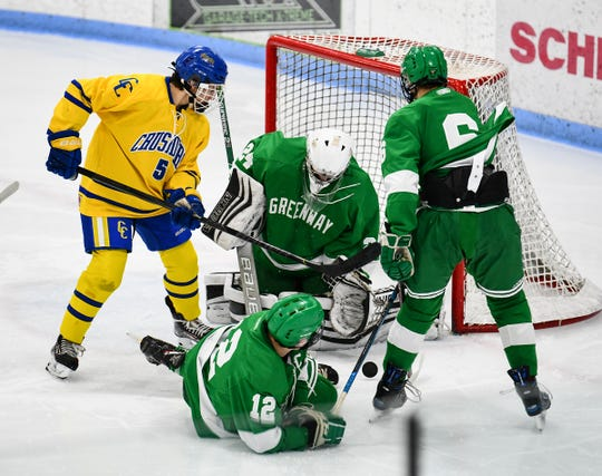 The puck bounces in front of Greenway goaltender Logan Wright and Cathedral's Nolan Widman during the Friday, Dec. 6, 2019, game at the MAC in St. Cloud.