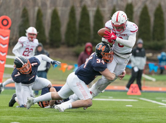 St. John's wide receiver Ravi Alston tries to catch a pass Saturday as Wheaton linebacker Ryan Schwartz tried to make the tackle. The Johnnies won, 34-33.