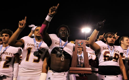 Florida High senior running back Alfred Menjor (middle) celebrates with the runner-up trophy in front of a cheering crowd after Florida High's football team fell 35-20 to Chaminade-Madonna in the Class 3A state championship game on Dec. 6, 2019 at Tallahassee's Gene Cox Stadium.