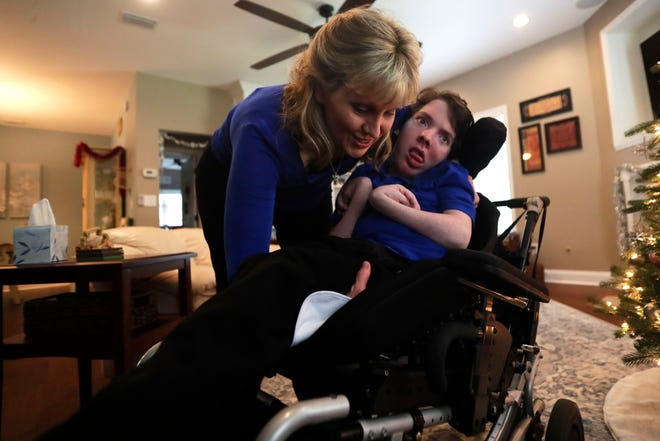 Sabrina Kimball places her. 22-year-old son Greyson, who has developmental disabilities, in his wheelchair.