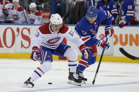 Dec 6, 2019; New York, NY, USA; Montreal Canadiens center Max Domi (13) plays the puck against New York Rangers defenseman Adam Fox (23) during the first period at Madison Square Garden. Mandatory Credit: Brad Penner-USA TODAY Sports