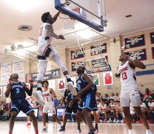 Stepinac's Adrian Griffin Jr. (21) stuffs a rebound during their 81-69 win over Monsignor Scanlan at Stepinac High School in White Plains on Friday, December 6, 2019.