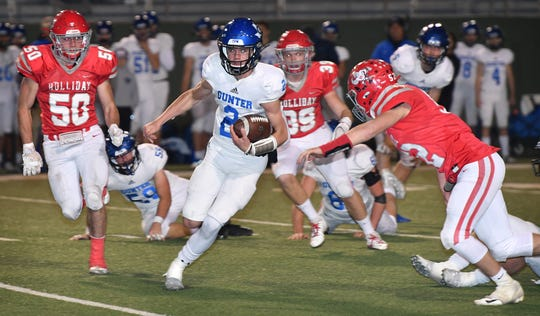 Several Holliday Eagles players try to corral Gunter quarterback Hut Graham (2) during first quarter action Friday night at Memorial Stadium.