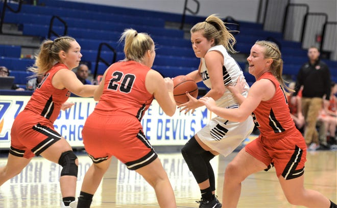 Zanesville's Melena Moore tries to make a play against three Coshocton defenders in Saturday's game. Zanesville won 67-23.