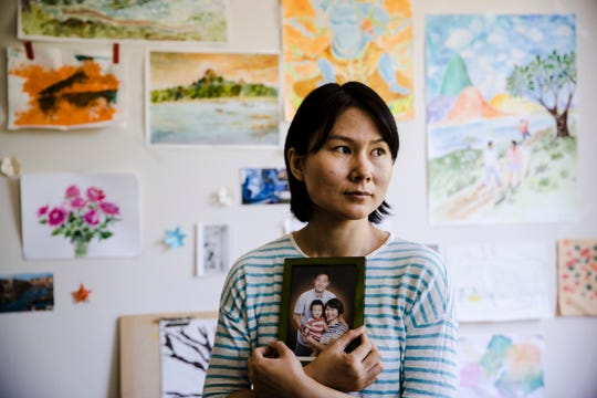 Hua Qu, the wife of  detained Chinese-American Xiyue Wang, poses for a photograph with a portrait of her family  on May 9, 2018.