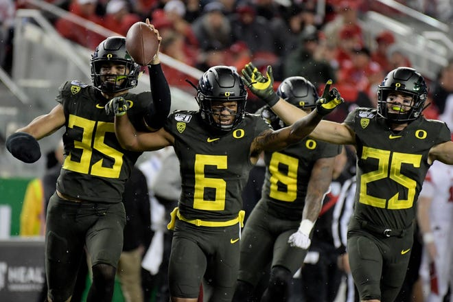 Oregon cornerback Deommodore Lenoir (6) celebrates with former teammates Troy Dye (35), Jevon Holland (8) and Brady Breeze during the 2019 Pac-12 championship game against Utah at Levi's Stadium.