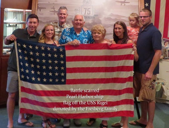 Home of the Brave museum owner Glenn Tomlinson, third left, poses with members of the Freiberg family, who donated a flag from the USS Rigel, one of the naval ships damaged in the attacks on Pearl Harbor on Dec. 7, 1941.