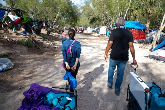 Volunteers with Acupuncturists Without Borders Victor Manuel, and Rocio Lopez walk thought the migrant camp in Matamoros, Tamaulipas.
