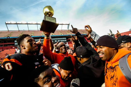 Woodrow Wilson football coach Preston Brown hoists the NJSIAA trophy after their 12-7 win over Wall in the South Group III regional championship game at High Point Solution Stadium in Pisacataway.