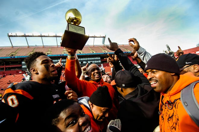Woodrow Wilson football coach Preston Brown hoists the NJSIAA trophy after their 12-7 win over Wall in the South Group III regional championship game at High Point Solution Stadium in Pisacataway on Dec. 8, 2019.