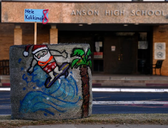 A surfing Santa Claus decorates a hay bale in front of Anson High School Saturday.