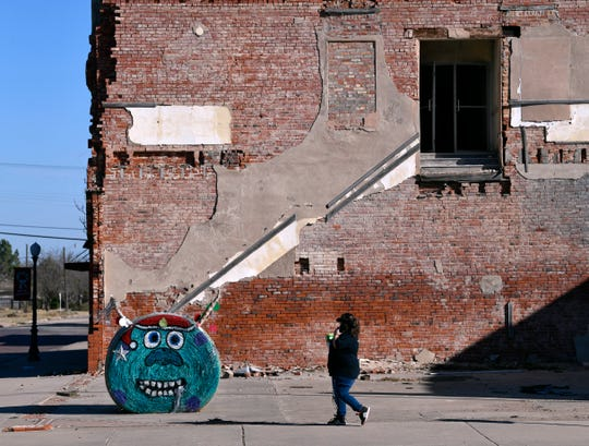 A pedestrian walks past a painted hay bale in Anson near the Jones County Courthouse square Saturday. Decorated hay bales can be found in Anson, Hawley and Stamford during the holidays.