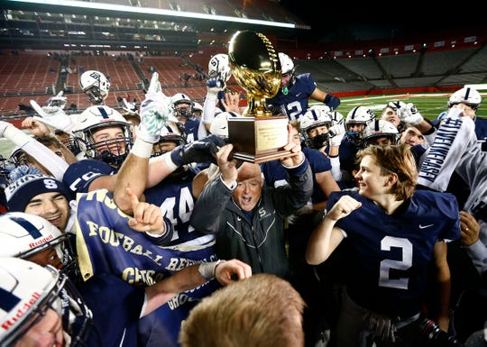 Shawnee High School football coach Tim Gushue hoists the trophy after winning the NJSIAA Group 4 Championship over Hammonton at SHI Stadium in Piscataway Saturday, December 7, 2019.