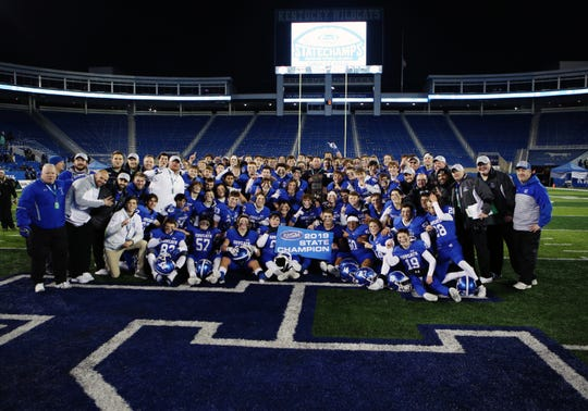 Covington Catholic players and coaches celebrate with their championship trophy from the KHSAA 5A state championship Dec. 7, 2019. Covington Catholic defeated Frederick Douglass 14-7.