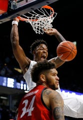 Xavier Musketeers forward Tyrique Jones (4) dunks over Cincinnati Bearcats guard Jarron Cumberland (34) as he's fouled in the second half of the Annual Crosstown Shootout rivalry game between the Xavier Musketeers and the Cincinnati Bearcats at the Cintas Center in Cincinnati on Saturday, Dec. 7, 2019. Xavier took the annual rivalry game, 73-66.