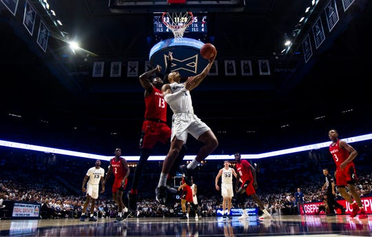 Xavier Musketeers guard Bryce Moore (11) hits a shot around Cincinnati Bearcats forward Tre Scott (13) in the first half of the NCAA basketball game between the Cincinnati Bearcats and the Xavier Musketeers on Saturday, Dec. 7, 2019, at the Cintas Center in Cincinnati. Xavier Musketeers defeated Cincinnati Bearcats 73-66.