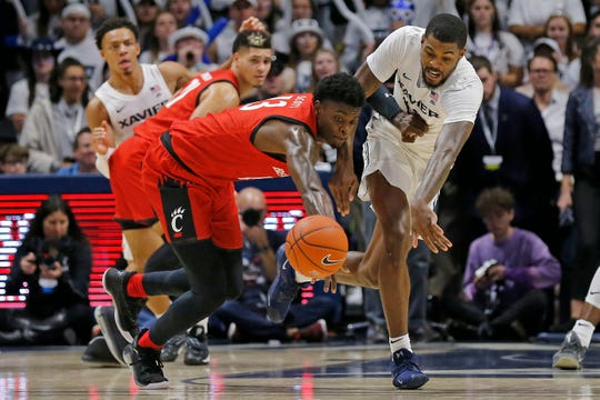 Xavier Musketeers forward Naji Marshall (13) and Cincinnati Bearcats forward Trevon Scott (13) chase a loose ball in the second half of the Annual Crosstown Shootout rivalry game between the Xavier Musketeers and the Cincinnati Bearcats at the Cintas Center in Cincinnati on Saturday, Dec. 7, 2019. Xavier took the annual rivalry game, 73-66.